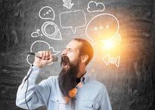 Homme d'affaires avec un microphone, bulles de la parole photographie stock libre de droits