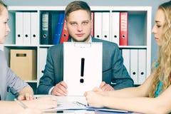 Homme d'affaires avec un point d'exclamation sur un presse-papiers regardant ses collègues lors d'une réunion d'affaires image libre de droits