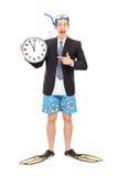 Homme d'affaires avec une prise d'air tenant l'horloge murale Photos stock