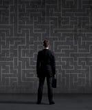 Homme d'affaires avec une serviette sur un labyrinthe Photographie stock