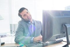 Homme d'affaires ayant l'appel téléphonique tout en à l'aide de son ordinateur Photographie stock