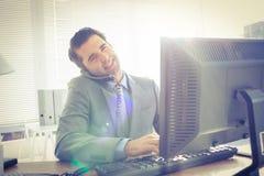 Homme d'affaires ayant l'appel téléphonique tout en à l'aide de son ordinateur Image libre de droits