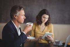 Homme d'affaires ayant le café tandis que collègue à l'aide du comprimé numérique photos stock