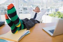 Homme d'affaires ayant un petit somme avec des pieds sur le bureau photo stock