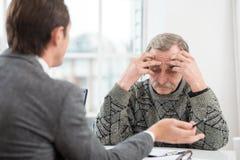 Homme d'affaires ayant une entrevue avec le vieil homme triste Images stock