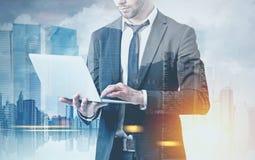 Homme d'affaires barbu avec un ordinateur portable dans une ville images stock