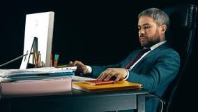 Homme d'affaires barbu bel travaillant à son ordinateur et détente Fond noir vidéo 4K banque de vidéos