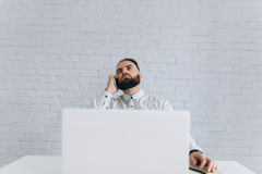 Homme d'affaires barbu bel travaillant avec l'ordinateur portable le bureau et en appelant Photographie stock