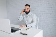 Homme d'affaires barbu bel travaillant avec l'ordinateur portable le bureau et en appelant Image stock