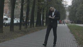 Homme d'affaires barbu dans l'allée de parc parlant par le téléphone clips vidéos