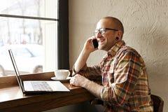 Homme d'affaires barbu de sourire portant l'habillement occasionnel de hippie utilisant le smartphone d'ordinateur portable et de photo stock
