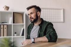 Homme d'affaires barbu de sourire regardant loin dans le bureau moderne Photo stock