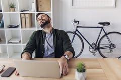 Homme d'affaires barbu dormant tout en à l'aide de l'ordinateur portable Photographie stock