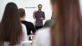 Homme d'affaires barbu en verres présentant le nouveau projet aux associés avec le tableau de conférence, entreprise constituée e clips vidéos