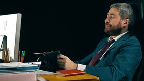 Homme d'affaires barbu fatigué baîllant à son bureau Fond noir tir 4k clips vidéos