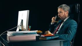 Homme d'affaires barbu focalisé travaillant à son lieu de travail et thé potable Fond noir tir 4k banque de vidéos