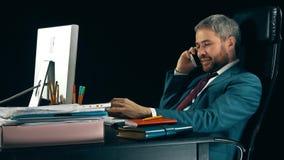 Homme d'affaires barbu gai travaillant sur son ordinateur et parlant au téléphone portable Fond noir vidéo 4K banque de vidéos