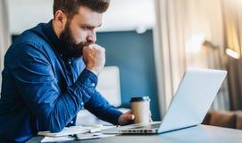 Homme d'affaires barbu sérieux travaillant sur l'ordinateur, café potable, pensant L'homme analyse l'information, vérifiant l'ema photos libres de droits
