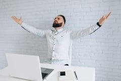 Homme d'affaires barbu s'asseyant à un bureau dans le bureau Image stock