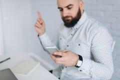 Homme d'affaires barbu s'asseyant à un bureau dans le bureau Image libre de droits