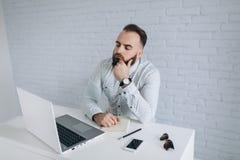 Homme d'affaires barbu s'asseyant à un bureau dans le bureau Photographie stock
