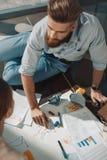 Homme d'affaires barbu s'asseyant sur le plancher et travaillant avec des graphiques de gestion Photo stock