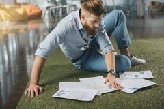 Homme d'affaires barbu s'asseyant sur le plancher et travaillant avec des graphiques de gestion Images libres de droits