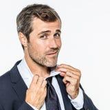 Homme d'affaires barbu sexy examinant son collier et cravate pour assurer l'élégance Image stock