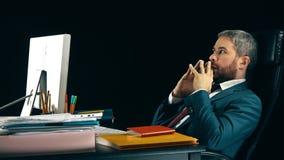 Homme d'affaires barbu songeur balançant sur sa chaise de bureau Fond noir vidéo 4K banque de vidéos