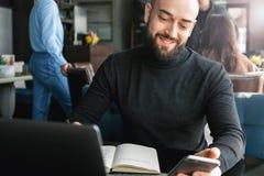 Homme d'affaires barbu travaillant sur l'ordinateur portable tout en se reposant en café, utilisant le smartphone, faisant des en image libre de droits