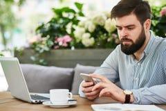 Homme d'affaires barbu utilisant Smartphone en café Images libres de droits