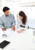 Homme d'affaires bel affichant un plan à son associé photo stock