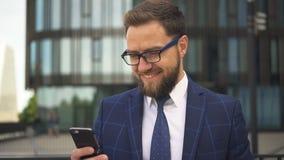 Homme d'affaires bel avec la barbe et dans le regard de sourire en verre à l'écran de son smartphone au district des affaires banque de vidéos