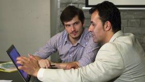 Homme d'affaires bel ayant une réunion avec son patron à l'aide de l'ordinateur portable ensemble banque de vidéos