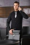 Homme d'affaires bel dans l'entrée de bureau avec le mobile Images stock