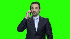Homme d'affaires bel dans le costume classique parlant sur le téléphone portable et le sourire banque de vidéos