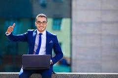 Homme d'affaires bel dans le costume et lunettes se reposant avec l'ordinateur portable Images libres de droits