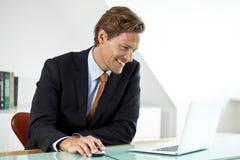 Homme d'affaires bel de Miling utilisant l'ordinateur portable dans le bureau Photos stock