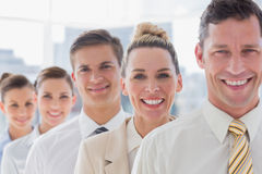 Homme d'affaires bel de sourire se tenant avec son équipe Images stock