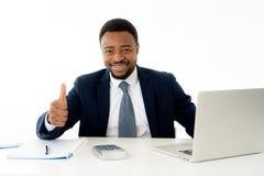 Homme d'affaires bel heureux attirant d'afro-américain travaillant sur l'ordinateur portable sur le bureau au bureau photos stock