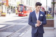 Homme d'affaires bel marchant par la ville Photographie stock