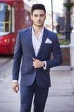 Homme d'affaires bel marchant par la ville Images stock