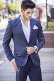 Homme d'affaires bel marchant par la ville Image stock