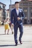 Homme d'affaires bel marchant par la ville Photographie stock libre de droits