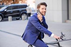 Homme d'affaires bel montant sa bicyclette Images stock