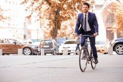 Homme d'affaires bel montant sa bicyclette Photographie stock