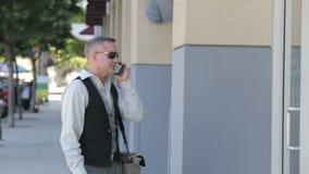 Homme d'affaires bel parlant au téléphone devant un immeuble de bureaux banque de vidéos