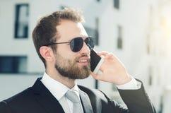Homme d'affaires bel parlant sur la ville de téléphone extérieure photographie stock libre de droits