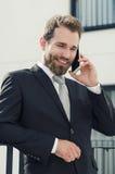 Homme d'affaires bel parlant sur la ville de téléphone extérieure images stock
