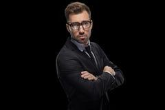 Homme d'affaires bel posant avec les bras croisés dans les lunettes et le costume noir Photographie stock